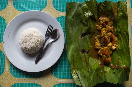 Indonesian dish PEPES IKAN on banana leaf on plate plus rice.