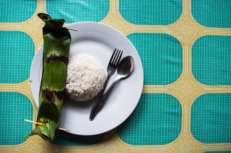 Indonesian dish PEPES IKAN closed in banana leaf - top view with rice and copy space right.
