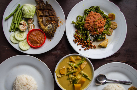 Indonesian food: Kankung plecing (spicy water spinach dish), Ikan goreng (fried fish) and kare (curry) top view. Banque d'images