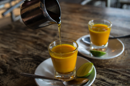 Adding honey to two healthy drinks. Shots in close-up without hand.