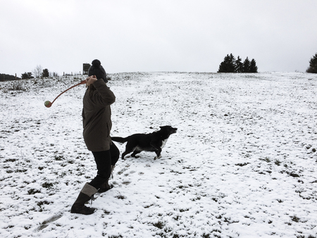 Woman playing fetch with dog on a dull winter day with copy space on the right. Stock Photo