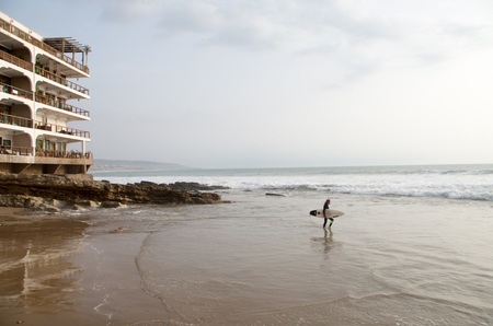 Surfer is going into the water to catch some waves in Taghazout, January 2018