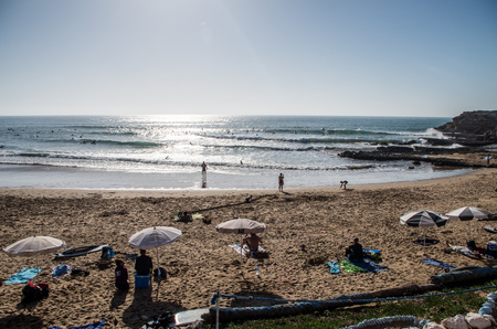People relaxing at the beach and surfing the waves at surf spot called Devils Rock in Morocco, January 2018.