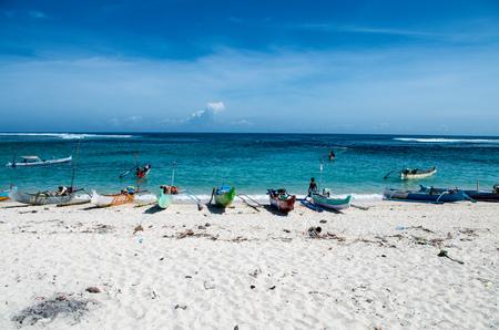 Traditional Indonensian fisher at work with their boats aligned on the beach in island Sumbawa in March 2017, Indonesia.
