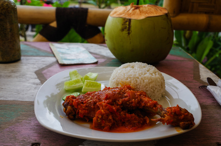 Typical Indonesian Dish: Nasi Ayam Plecing (Chicken with rice and special sauce) and young coconut.