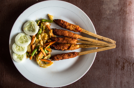 Indonesian dish Lombok: Sate Pusut (marinated meat mix on stick) birds eye. Stock Photo
