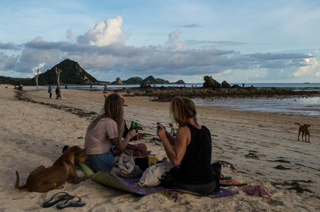 Group of people chilling at the beach with wild dogs wanting to join at Kuta Beach, Lombok, Indonesia, March 2017.
