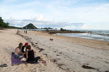 View along Kuta beach with a group of people chilling at Kuta Beach, Lombok, Indonesia, March 2017. Éditoriale