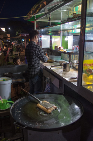 Man prepares Martabak Telur in his shop at night on the streets of Kuta, Lombok (Indonesia), March 2017 - vertical.