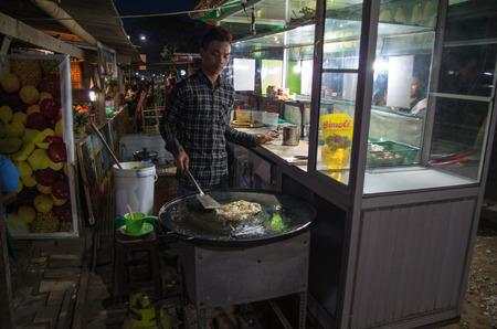 Man prepares Martabak Telur at night on the streets of Kuta, Lombok (Indonesia), March 2017.