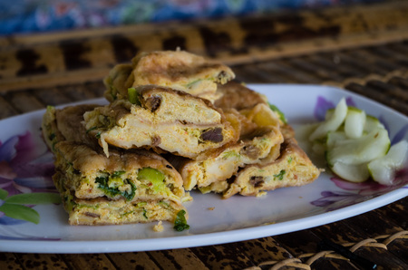 MARTABAK TELUR - stuffed pancake or pan-fried bread Indo-style on a plate, close-up.