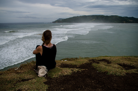 Woman melancholically looking at the ocean in Lombok (Seger beach, Kuta).