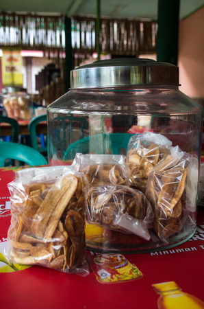 Container with banana chips / keripik pisang presented in a local Indonesian restaurant, Kuta, Lombok Indonesia, March 2017.