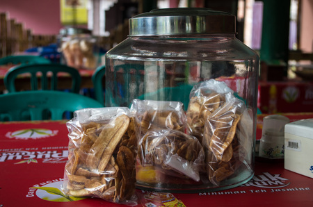 Container with banana chips / keripik pisang presented in a local Indonesian restaurant, centered, Kuta, Lombok Indonesia, March 2017.