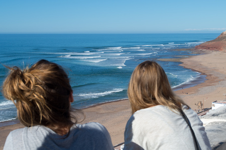 Two people looking at the waves in Sidi Ifni, Morocco.