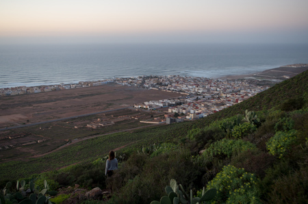 Woman enjoying the sunset with view towards Sidi Ifni. Banque d'images