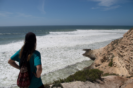 Woman checking out the surf at Killer Point surf spot near Taghazout.