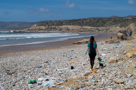 Woman waling along beach with a lot of rubbish, copy-space left.