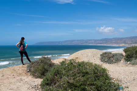 Woman looking at the coastline from Killer Point surf spot. Standard-Bild