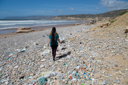 Woman waling along beach with a lot of rubbish.