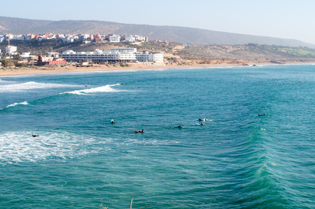 Surfers paddling back after wave at surf spot called Banana Point in Morocco, January 2018.