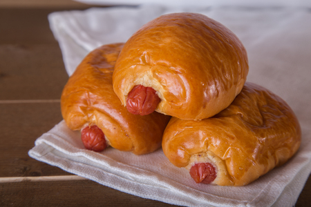 l plate: two sausage breads on white linen  wooden background