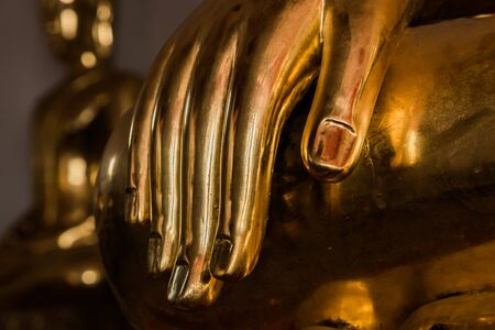 close up of Buddha statue focus at hand low key Stock Photo