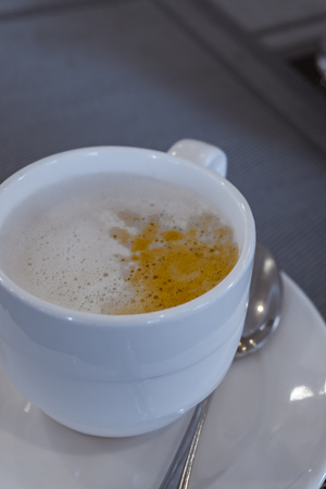 cup of coffee and milk foam topping on the table with spoon and saucer  close up selective focus