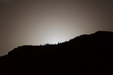 cliff edge: Moon rising behind a cliff edge  vegetated with trees