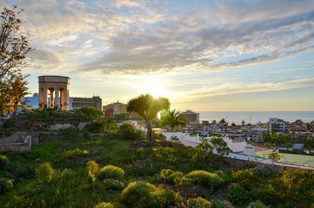 sordid: Beautiful garden and temple front of sun sunset and city - Puerto de la Cruz Editorial
