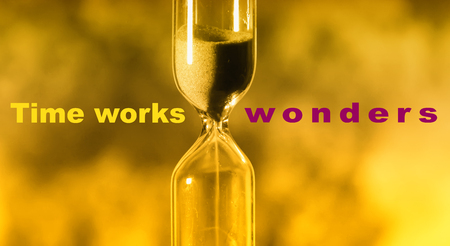 glass hourglass is pouring out the sand expires time. Time works wonders