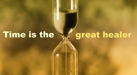 glass hourglass is pouring out the sand expires time. Time is the great healer Stock Photo