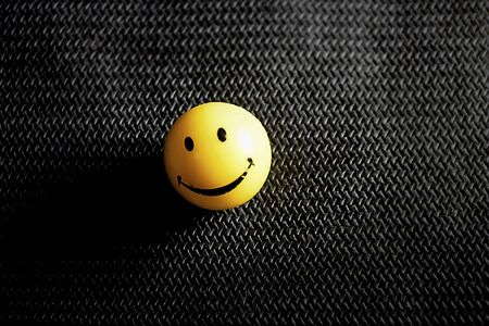 smiley face ball background. toy smiley yellow. gray background.