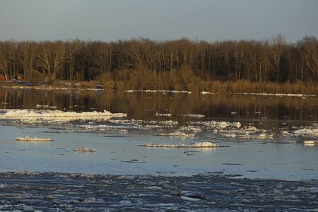 ice drift on the river. sunset. ice floes floating on the water. spring melts the ice cracks