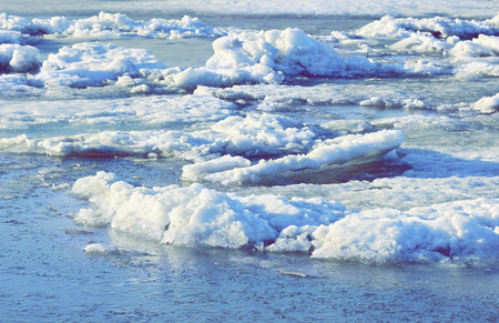 large pieces of ice are white.ice drift on the river. large ice floes floating on the water. spring is melting ice cracking.
