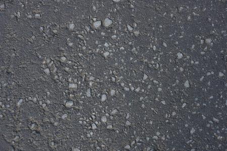 the dark gray asphalt texture background rocks interspersed with gravel dirt sand 写真素材