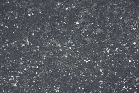 the dark gray asphalt texture background rocks interspersed with gravel old dirty sand 写真素材
