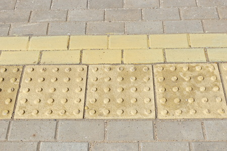 yellow tactile path for people with disabilities on the platform of the railway station. summer day