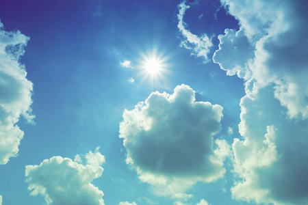 clouds are white blue the sky is blue the sun is shining from behind the clouds a summer day.Clouds around the sun 版權商用圖片