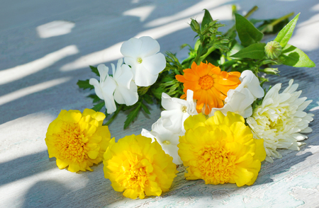 bouquet of summer flowers on a white wooden table. yellow white orange flowers Astra marigolds Phlox calendula
