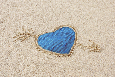 heart drawn on the sand pierced by an arrow in her splashing sea memories of a wonderful holiday concept a piece of the sea I will take with me