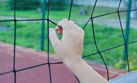 volleyball boy's hand holding a volleyball net close-up 스톡 콘텐츠