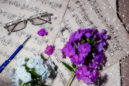 music search. old sheet music glasses purple and white flowers concept classical music close-up