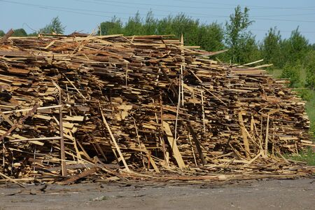 waste from sawing logs. stacks of thin boards waste wood warehousing. waste from sawing logs. stacks of thin boards waste wood warehousing. forest industry waste pollution Archivio Fotografico
