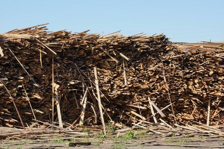 waste from sawing logs. stacks of thin boards waste wood warehousing. waste from sawing logs. stacks of thin boards waste wood warehousing. forest industry waste pollution