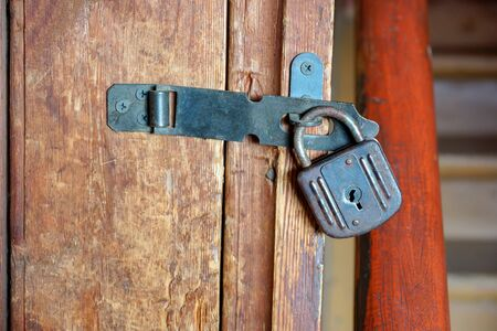 old small lock hanging on the pantry door closeup wooden background old door ladder heck
