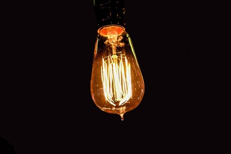 Old vintage Edison light bulb on background with space for text, concept of creativity, incandescent lamp