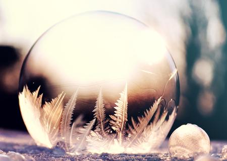 Paarse bevroren zeepbelbal op sneeuw in zonsondergang, kristalvorming, winterachtergrond met exemplaarruimte Stockfoto