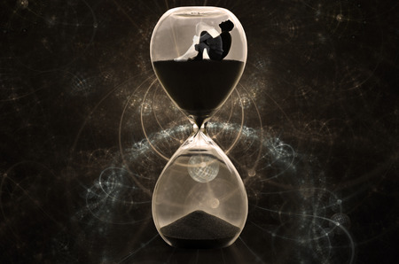 Alone man sitting in hourglass, man looking up to the sky in the dark. Time traveling with sand watch. 免版税图像