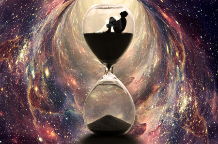 Alone man sitting in hourglass with a ghost woman, boy looking up to the sky in the dark. Time traveling with sand watch in wormhole between galaxies 免版税图像